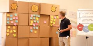 Ein Trainer arbeitet an einer Wand aus Pappwürfeln mit Post-its.